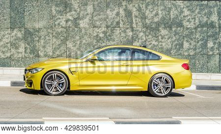 Yellow Bmw M4 Coupe F82 Parked On The Background Of Granite Wall, Side View. Moscow, Russia - July 2