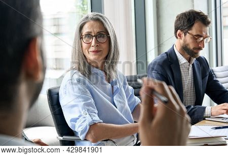 Smiling Mature Caucasian Female Executive Manager Wearing Glasses Looking At Male Manager Discussing