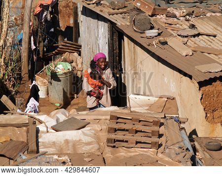Soweto South Africa, August 15 2007; Woman Holds Baby By Door To Her Shanty Town Home In Area Of Som