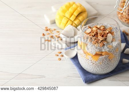 Delicious Chia Pudding With Granola And Mango On White Wooden Table, Space For Text