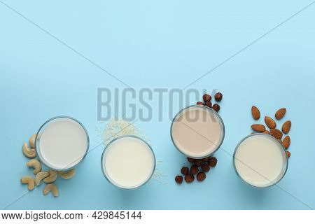 Different Vegan Milks, Nuts And Rice On Light Blue Background, Flat Lay. Space For Text