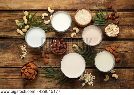 Different Vegan Milks And Ingredients On Wooden Table, Flat Lay