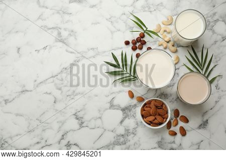 Different Vegan Milks And Ingredients On White Marble Table, Flat Lay. Space For Text