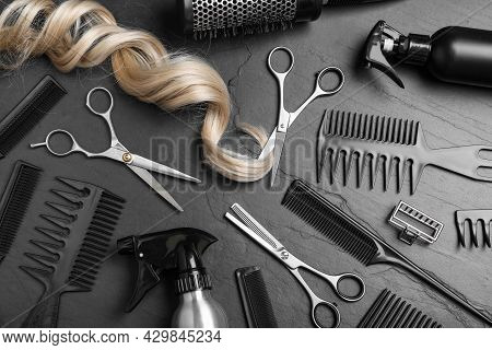 Flat Lay Composition Of Professional Scissors, Hair Strand And Other Hairdresser's Equipment On Blac