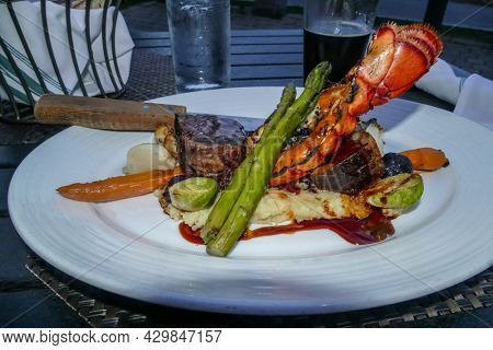 Lobster tail with steak on dish with asparagus