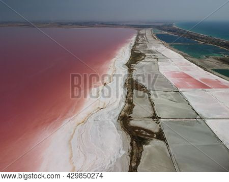 Flying Over A Pink Salt Lake. Salt Production Facilities Saline Evaporation Pond Fields In The Salty