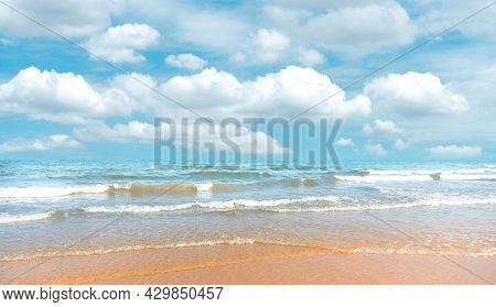 Smooth Brown Sand Beach On Blue Sea Water And White Wave Under White Fluffy Clouds And Pastel Blue S