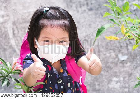 Happy Child Wearing 3d Medical Face Mask For Protection Spread Virus Pneumonia And Giving A Thumbs-u