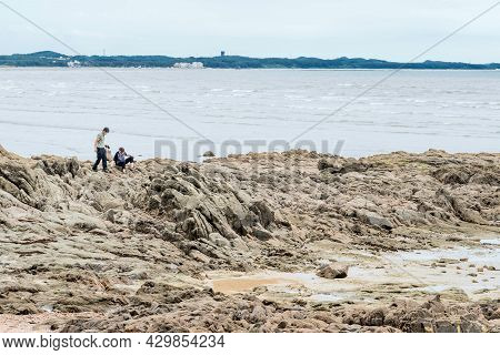 Taean, South Korea; July 30,2021: Unidentified People On Stony Outcropping Of Beach At Low Tide