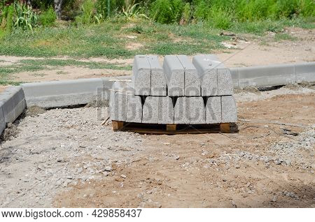 New Gray Curbs Are Stacked On A Wooden Pallet. Curbs Are Used As A Separator Between The Roadway And