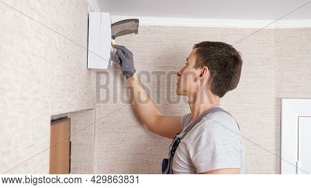 Concentrated Young Electrician In Gloves And Uniform Checks Contemporary Switchboard Above Front Doo