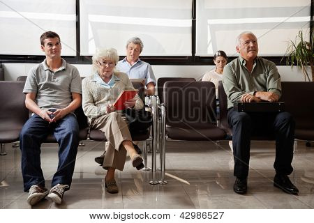 Portrait of senior woman with other people waiting for the doctor in hospital lobby