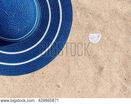 Horizontal Shot: Blue Straw Hat And Seashell On Golden Sand At The Beach, Copy Space For Text. Sun P
