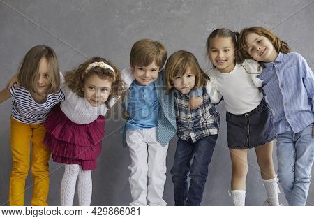 Group Portrait Of Happy Little Children Standing In Studio, Huddling And Smiling