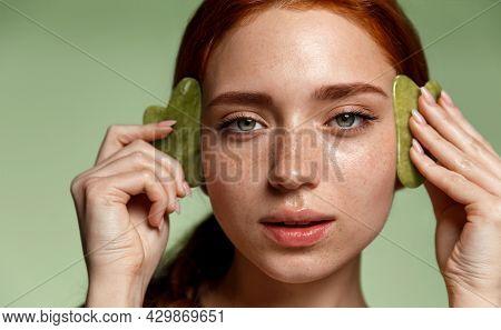 Close Up Face Of Young Beautiful Redhead Woman Massage Gua Sha With Jade Stone, Guacha Scrapper Mass