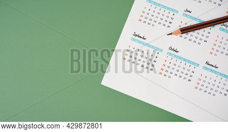 Top View Of Pencil On White Calendar And Green Background For Planning Work ,monthly Or Yearly Sched