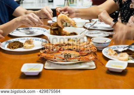 Asian Family Having Dinner With Fresh Steamed Blue Crabs Seafood At Home