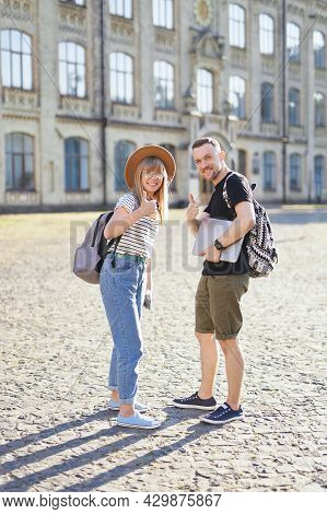 International Successful Students Couple Smiling Showing Thumbs Up Sign At The Camera. Two Attractiv