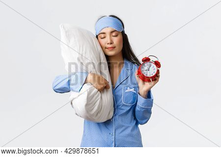 Cute And Silly Asian Girl In Blue Pyjamas And Sleeping Mask, Sleeping On Pillow With Closed Eyes And