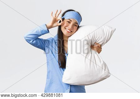 Satisfied Happy Smiling And Cute Asian Girl In Blue Pyjama And Sleeping Eyemask, Hugging Pillow In M