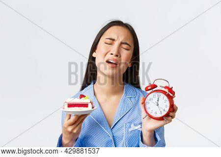 Close-up Of Displeased Asian Girl In Blue Pajama Express Regret As Cant Eat Delicious Piece Of Cake