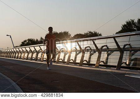 Evening Run. Athletic Guy Run On Promenade. Running Man. Evening Runner. Jogging Activities