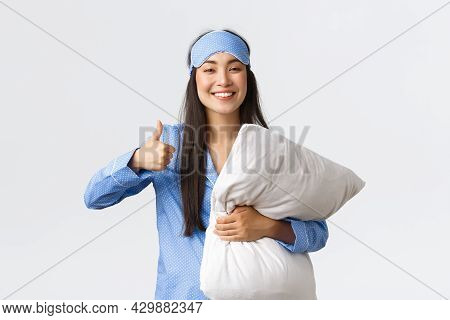 Cheerful Pleased Cute Asian Girl In Blue Pajama And Sleeping Mask, Holding Soft Comfortable Pillow A