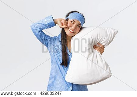Smiling Pleased Asian Girl In Sleeping Mask And Pyjamas, Lying In Bed And Hugging Pillow, Stretching