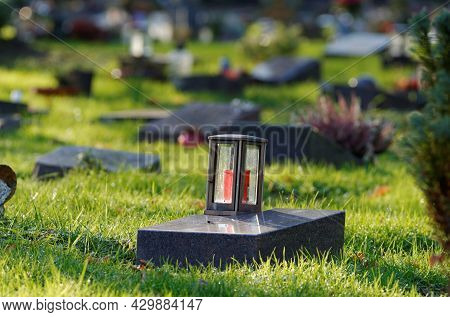 Lantern On A Gravestone Of A Cemetery With Pauper Graves Against Blurred Background