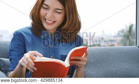 Young Asian Woman Reading Book On Cozy Couch Sofa At Warm Hom. Relax Woman Holding Book Read On Sofa