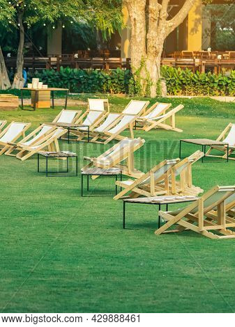 Many Empty White Deck Chairs With Tables In Lawn Is Surrounded By Shady Green Grass. Comfortable On