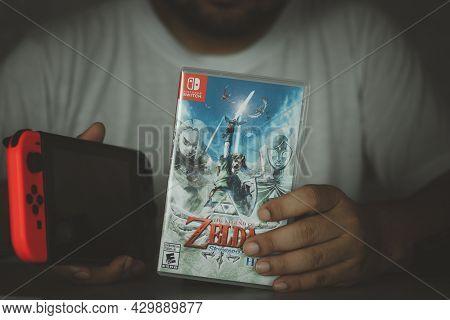 Samut Prakan, Thailand - August 15, 2021 : Man Holding Nintendo Switch Gaming Box Of The Legend Of Z