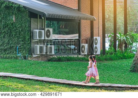 Asian Young Girls In Dress Walking Side By Side On Pathway Through Green Garden.two Girl Friends Wal