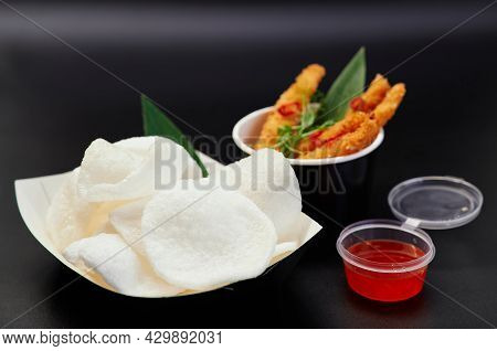 Krupuk Or Chinese Traditional Chips With Sauce And Shrimps In Tempura On Black Background. Junk Food