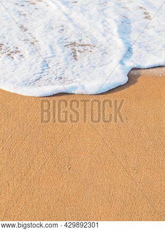 Vertical Shot: Sea Foam Wave On A Sandy Beach, Copy Space