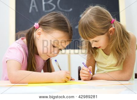 Cute little girls are writing using a pen in preschool