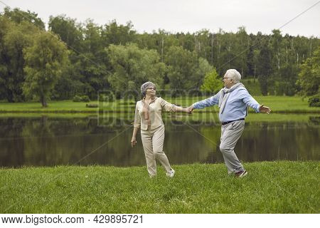 Happy Senior Couple Taking A Stroll By The River In A Green Park On A Nice Summer Day