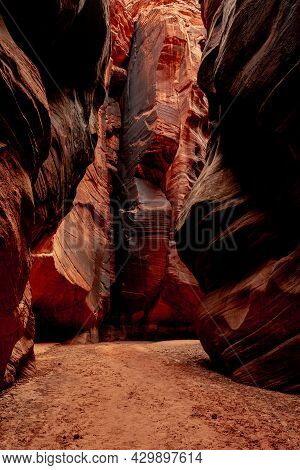 Orange Rock Wall Stained With Desert Varnish Glows At The End Of A Canyon In Buckskin Gulch