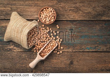 Dry Chickpeas On A Wooden Background With A Linen Bag And A Scoop. Top View, Copy Space.