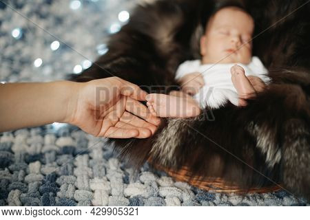 Close-up. Mother Caresses A Sleeping Newborn Baby.