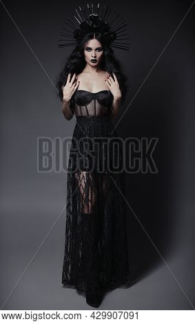 Halloween Theme: Beautiful Young Witch In Black Dress And Headwear With Roses And Spikes. Dark Beaut