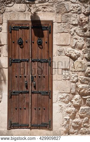 Entrance Door Of Traditional Middle Eastern Stone House. Iron Wrought Wooden Door On A Street Of Mid