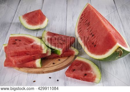 Close-up Of Sliced Pieces Of Ripe Red Watermelon On A Light Wooden Surface. Healthy Food Concept, Su