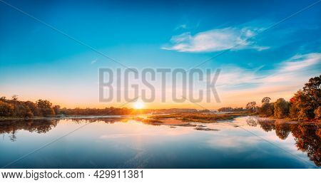 Panorama Of Autumn River Landscape In Belarus Or European Part Of Russia At Sunset. Sun Shine Over B