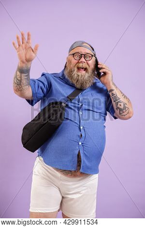 Jouful Plump Man Talks By Phone And Waves Hand Standing On Purple Background