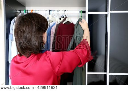 Woman Choosing An Outfit From Her Wardrobe. Girl In Red Nightie Standing In Front Of Hanger Rack And