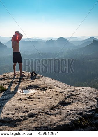 Athlete Hiker Takes Off His Sweaty Shirt On Top Of The Mountain. Hot Summer Day In Mountains.