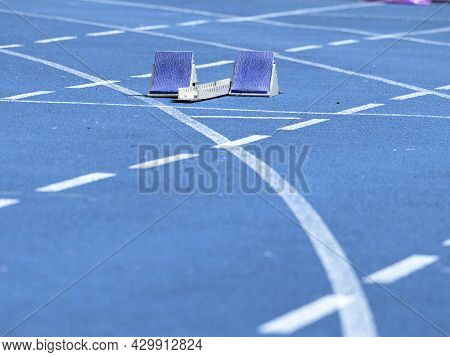 Starting Blocks Ready On Blue Running Tracks Lanes At Track And Field Stadium. Sport Accessory.