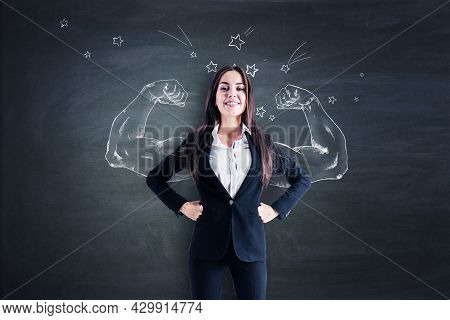 Happy Young European Businesswoman Standing On Chalkboard Wall Background With Drawn Muscle Hands. S