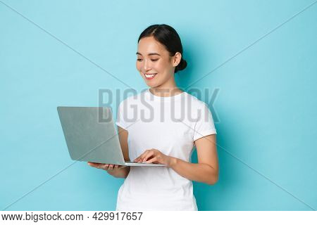 Smiling Pretty Asian Girl In White T-shirt, Working On Project, Looking Satisfied And Happy At Lapto
